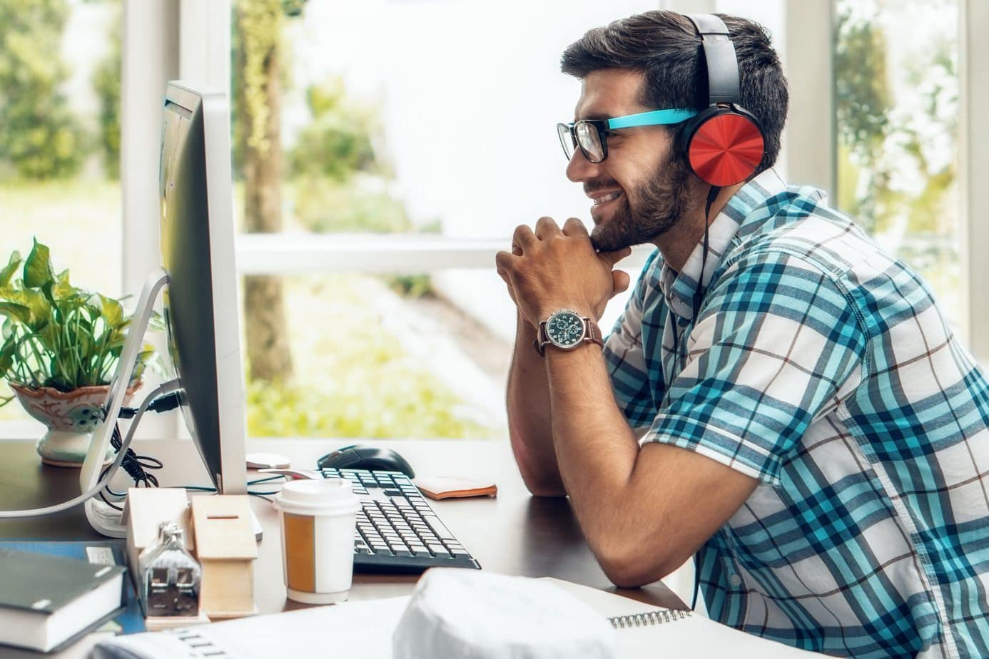 smiling man while listening to music on the computer